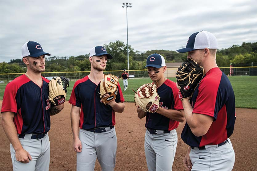 four baseball players with Rawlings and Wilson gloves