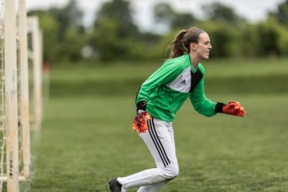 soccer goalkeeper wearing a green goalkeeper shirt and red goalkeeper gloves runs on the soccer field
