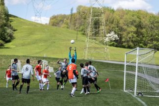 soccer players going for the ball goalkeeper leaps in the air for a high cross
