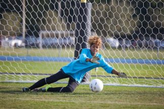 soccer goalkeeper wearing a blue goalkeeper shirt and black goalkeeper gloves dives for the soccer ball on the soccer field