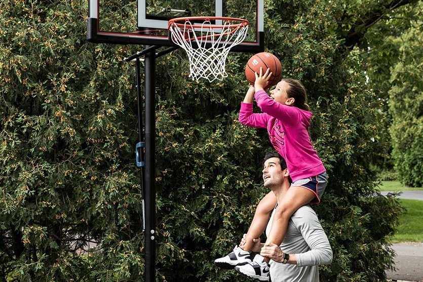dad lifts daughter up who is holding basketball to shoot in basketball hoop