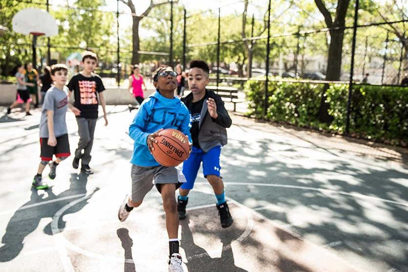 kids playing basketball outside on a basketball court