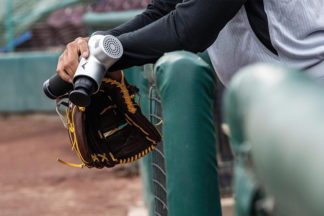 Baseball Player Holding Hyperice Percussive Therapy Device