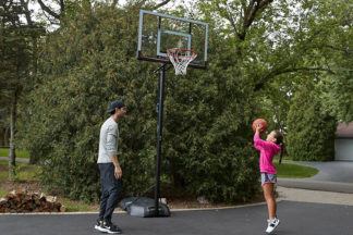 father rand daughter shooting a basketball in their driveway at a portable basketball hoop