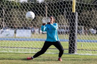 soccer goalkeeper makes save on soccer field with blue soccer goalkeeper shirt and goalkeeper gloves