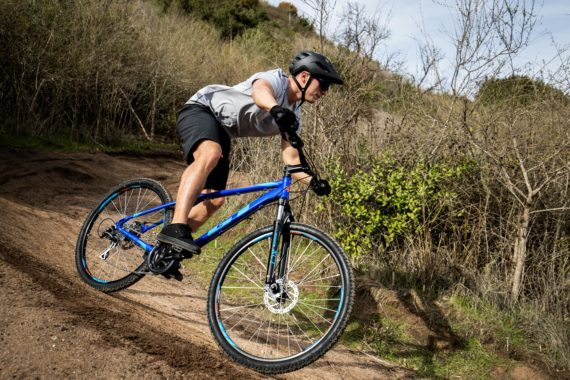 Man riding his blue GT Men's Aggressor Pro Mountain Bike