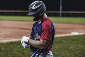 baseball player on a baseball field adjusting his white baseball gloves