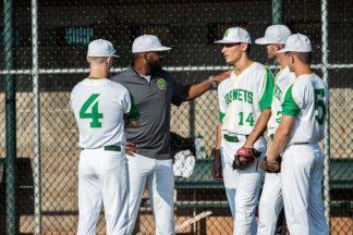 a baseball coach talks with his team during a baseball game