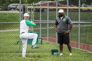 Baseball Pitcher Warming Up While Coach Watches