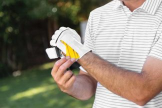man fastens golf training aid glove before taking to the golf course