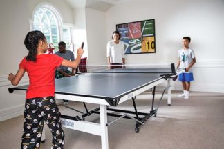 a family playing table tennis with the The Prince Tournament table