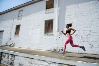 Woman running wearing Calia apparel and Brooks Adrenaline GTS 20 running shoes