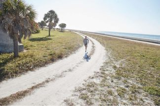 man running in Florida on a trail with trail running shoes