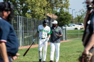 baseball player walks with his baseball coach down the sideline of the baseball field