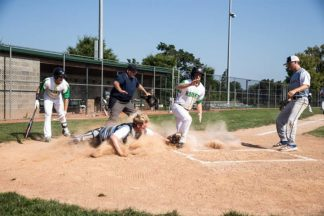 a baseball player slides into home base on the baseball field