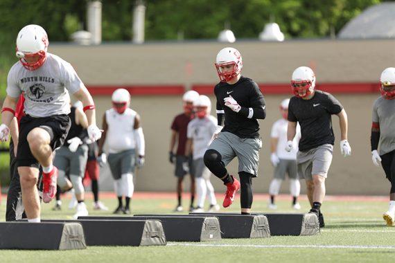 football players at football practice running agility bag drills