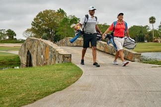 Two Golfers Walking On Golf Course And Carrying Golf Bags