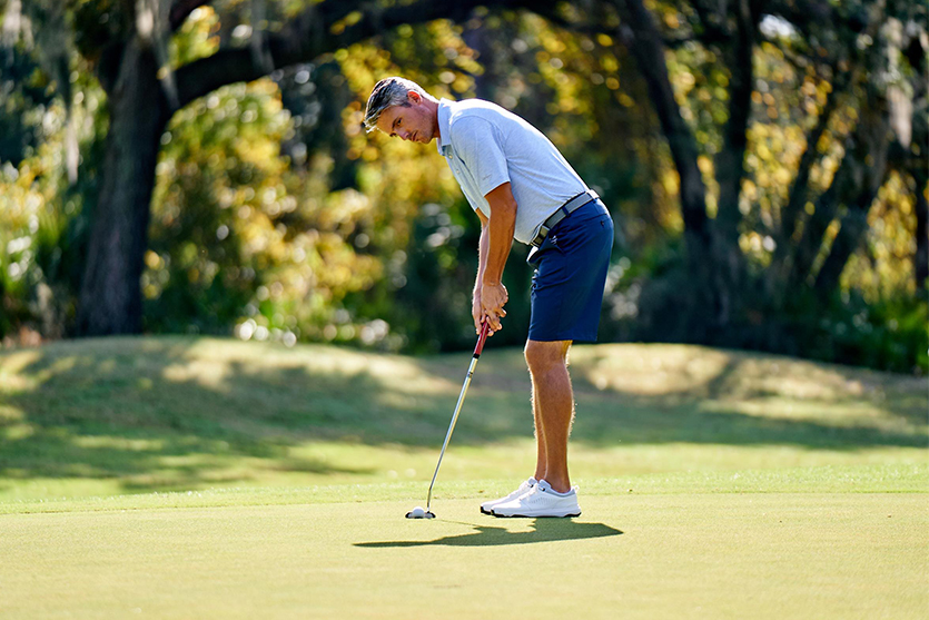 Male Golfer Putting On Golf Course