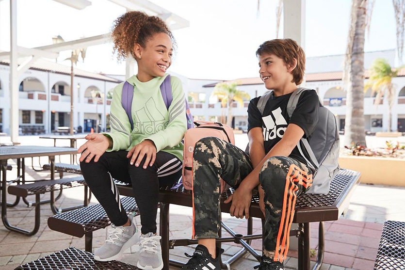 Two school kids sitting on a table wearing backpacks.