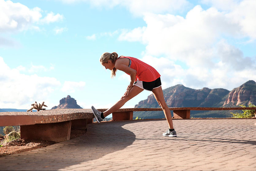 A woman stretching during a run.