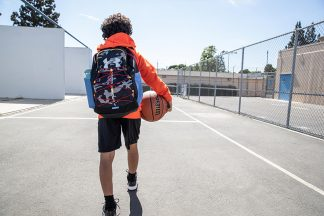 young kid wearing a backpack on a basketball court