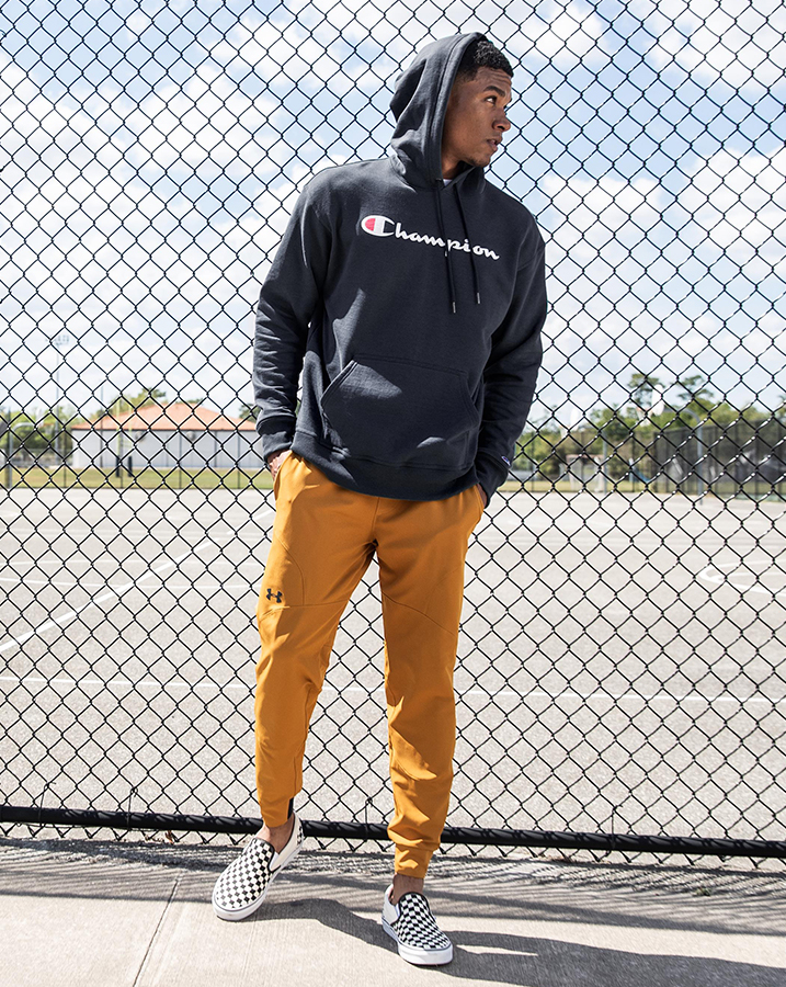 Male student wearing The Champion Powerblend Script Hoodie, Under Armour Stretch Utility Jogger, Vans Checkerboard Slip-On Shoes and the Carhartt Trade Plus Backpack