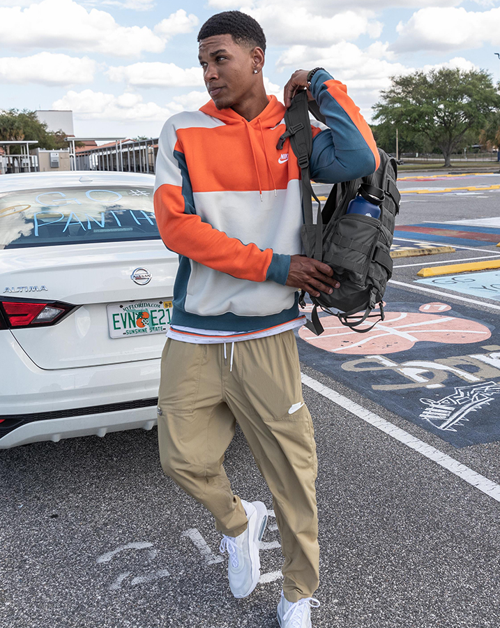 Male student going back to school wearing a color-blocked Nike Sportswear Hoodie, Nike Sportswear Woven Pants, Nike Sportswear RPM Backpack and Nike Air Max 2090 Shoes.