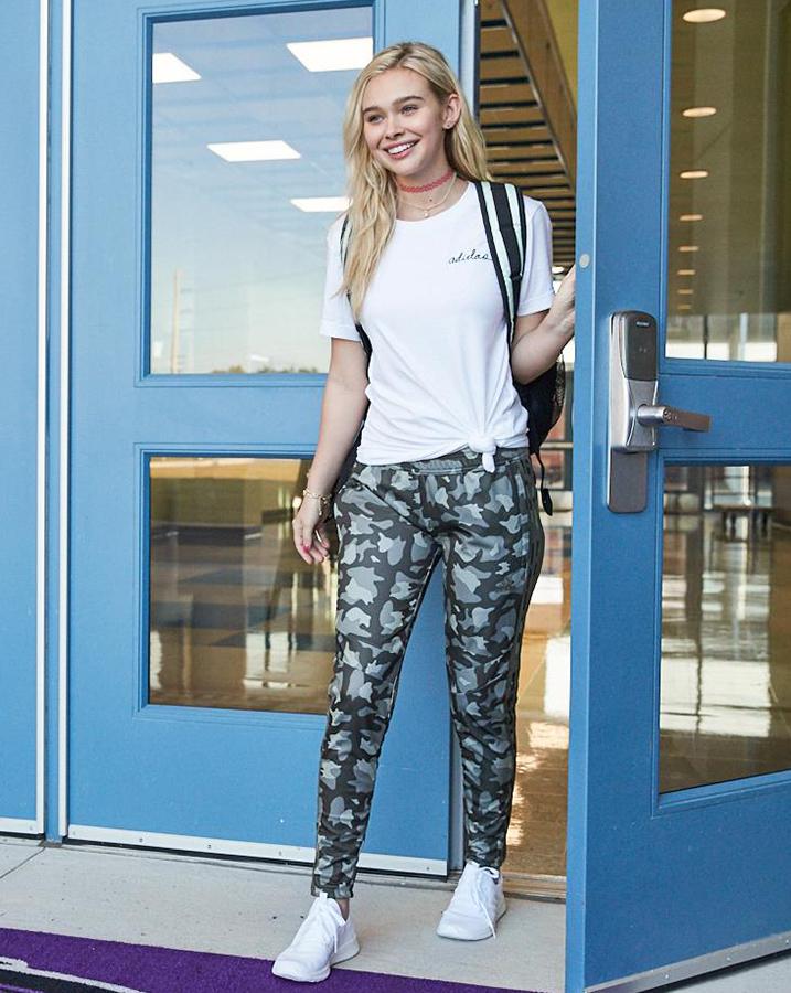 Female student wearing adiScript Boyfriend T-Shirt with the Tiro19 Camo Training Pants, Originals NMD_R1 shoes and Originals Tinted Festival Crossbody Bag.