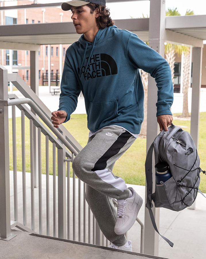 Teenage boy going back to school wearing The North Face Half Dome Hoodie, The North Face Hit Long Sleeve T-Shirt, The North Face Mudder Trucker Hat, Nike Sportswear Club Jogger Pants, The North Face Jester Backpack and Nike Air Force 1 '07 Shoes.