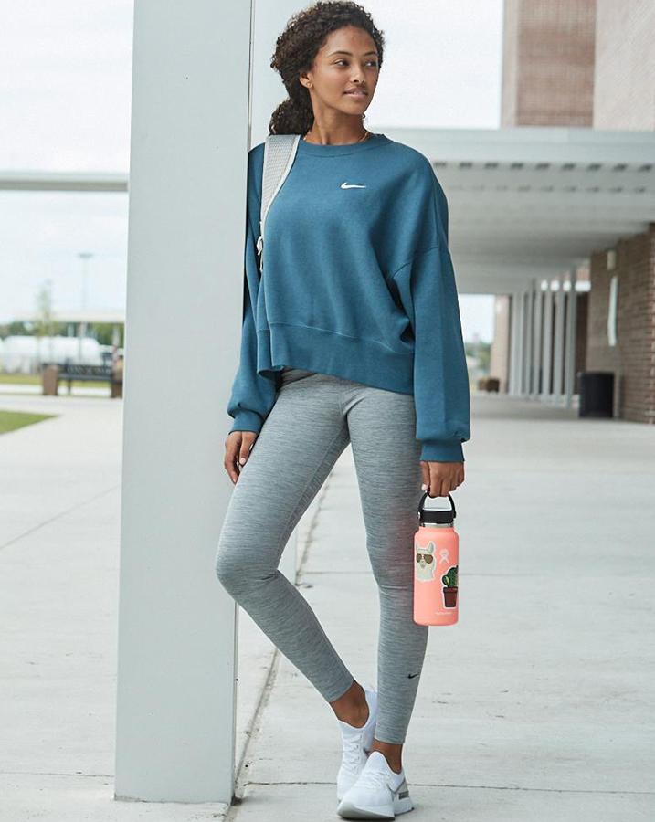 Female student wearing Nike Sportswear Essentials Fleece Cropped Crew, Nike Soft Sports Bra, Nike Air Tote Bag and Nike React Infinity Run Flyknit Running Shoes.