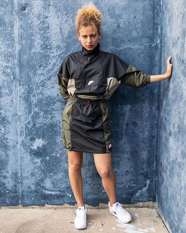 Female student wearing Nike Sportswear Woven Anorak Jacket and the Nike Sportswear Woven Skirt