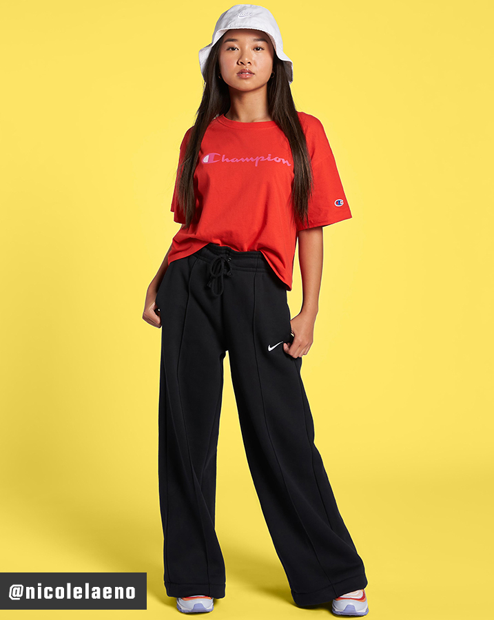 Nicole Laeno wearing Champion Cropped Script Logo Short Sleeve T-Shirt, wide-legged Nike Sportswear Trend Essential Fleece Wide Pants, a Nike bucket hat and the Nike Air Max 97 Shoes.