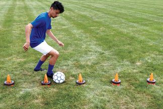male soccer player training with soccer training cones