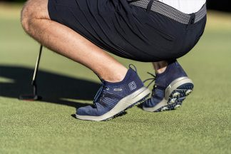 A man kneeling in golf shoes.