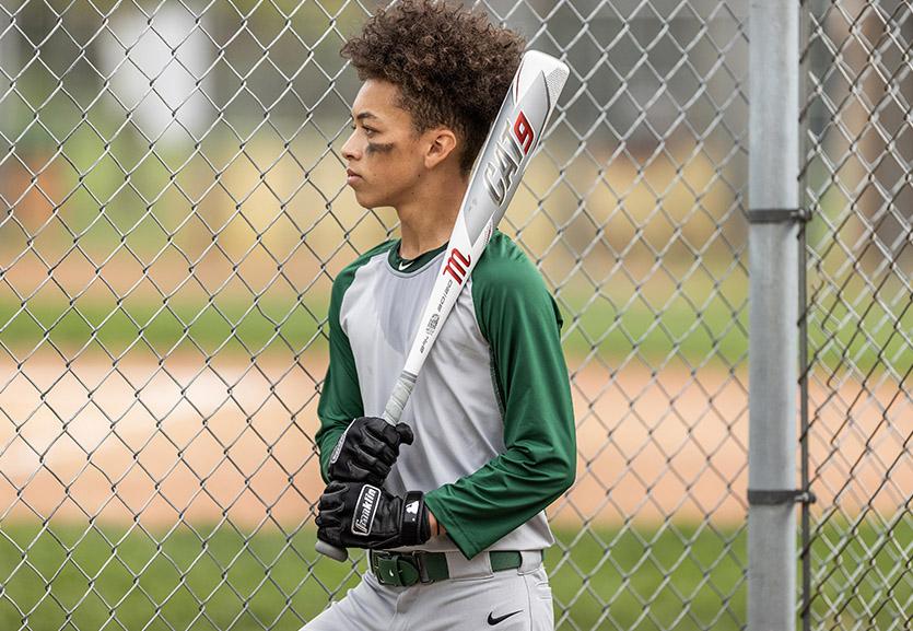 young baseball player holding a baseball bat