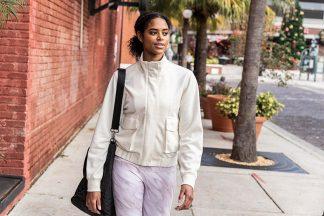 Woman walking down the street wearing white CALIA by Carrie Underwood Journey Cargo Jacket