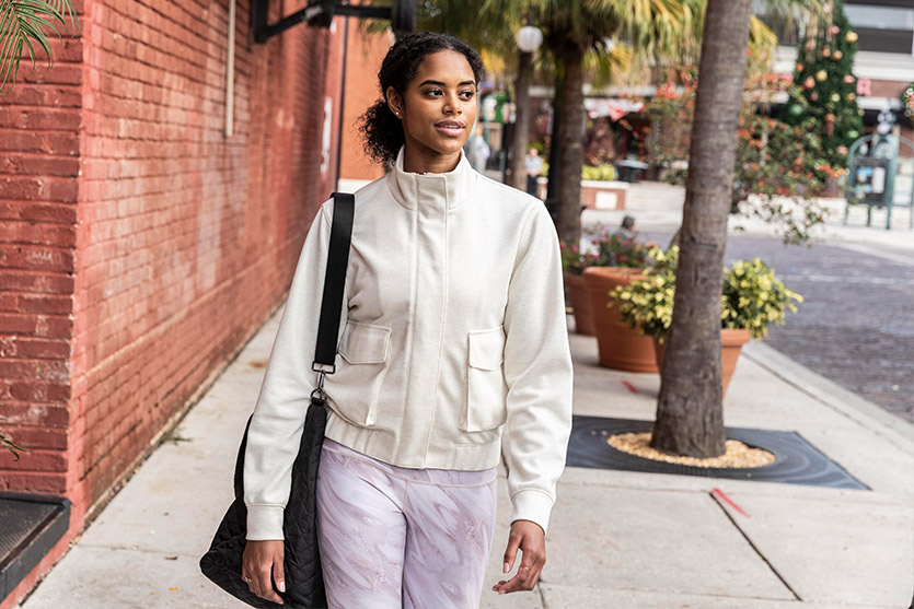 Woman walking down the street wearing white CALIA by Carrie Underwood Journey Cargo Jacket
