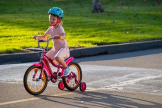 little girl riding a Nishiki Girls' Pueblo 20'' Mountain Bike on the road